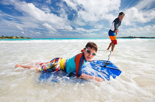 Son boogie boarding with his father stock photo