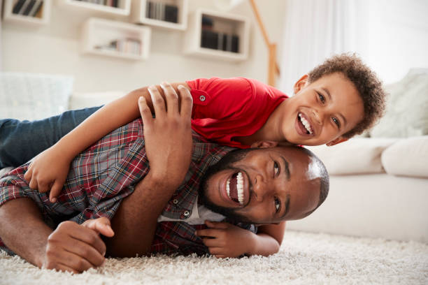 son climbs on fathers back as they play game in lounge together - wrestling stock pictures, royalty-free photos & images