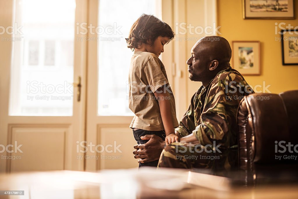 Son, daddy has to go to defend the country. stock photo