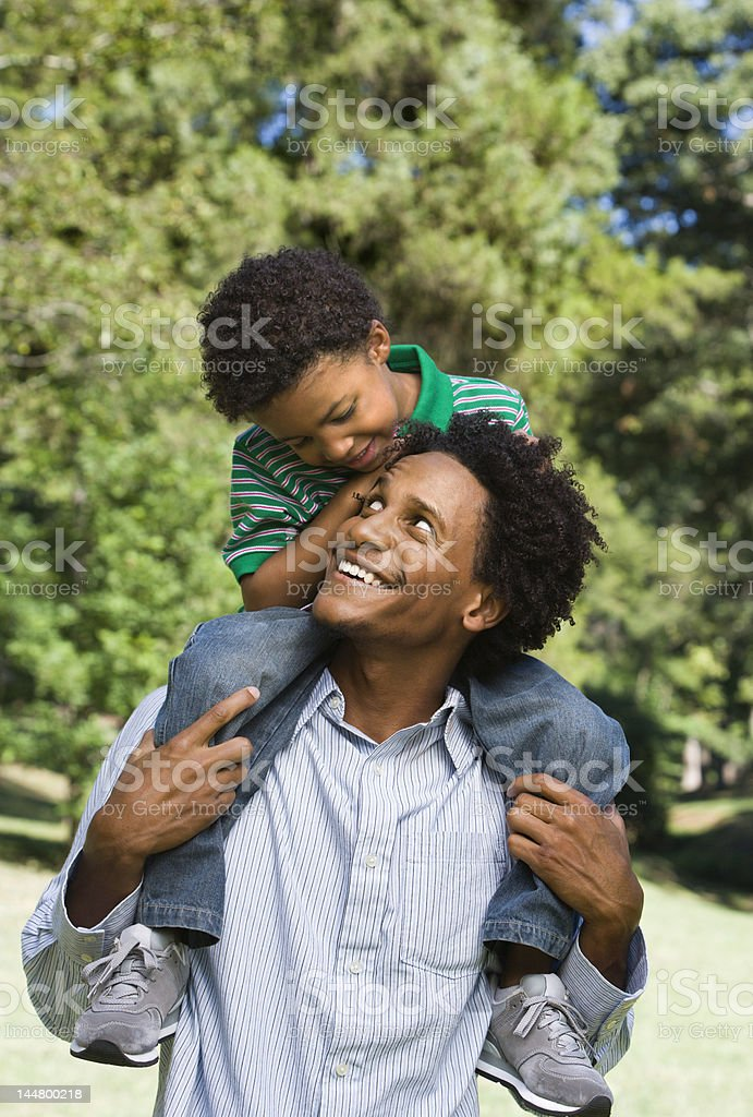 Son getting piggy back ride from dad in a park stock photo
