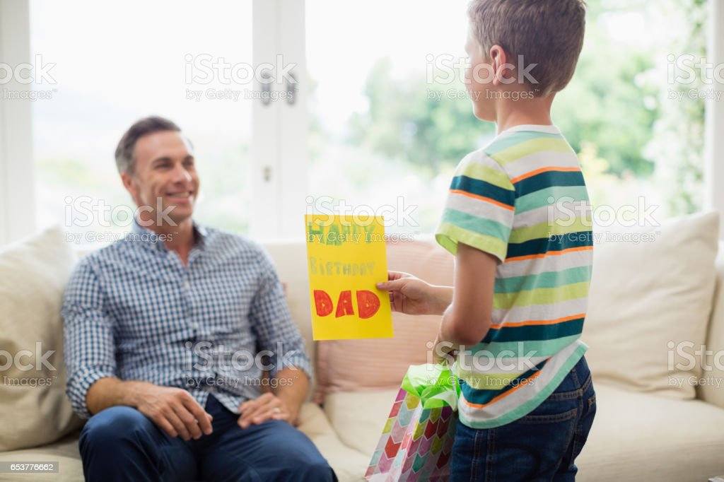 Son Giving Birthday Card To Father In Living Room Royalty Free Stock Photo