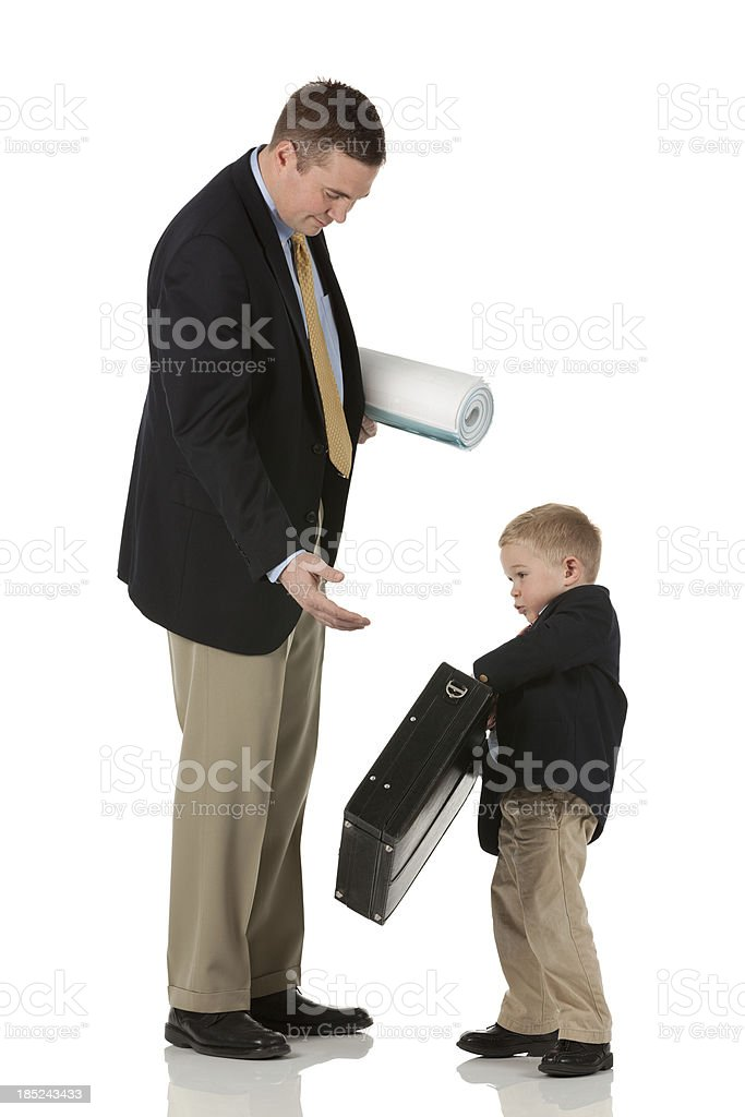 Son giving briefcase to his father royalty-free stock photo