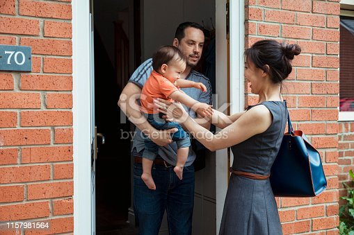 A father is standing in the doorway of their home with his son as he greets his mother upon her return from work.