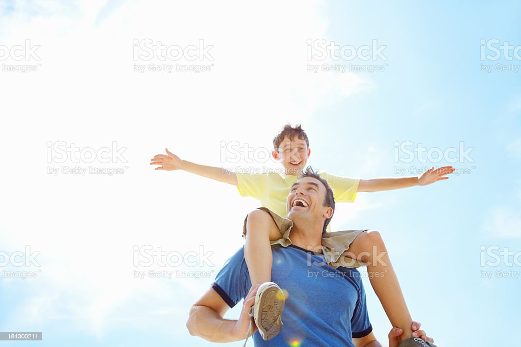 Son having fun sitting on his father's shoulders stock photo