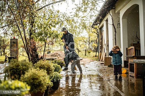 istock Son helping father and sweeping water from front yard on rainy day 1224471637