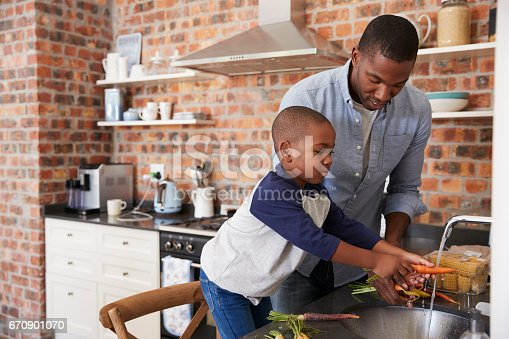 istock Son Helping Father To Prepare Vegetables For Meal In Kitchen 670901070