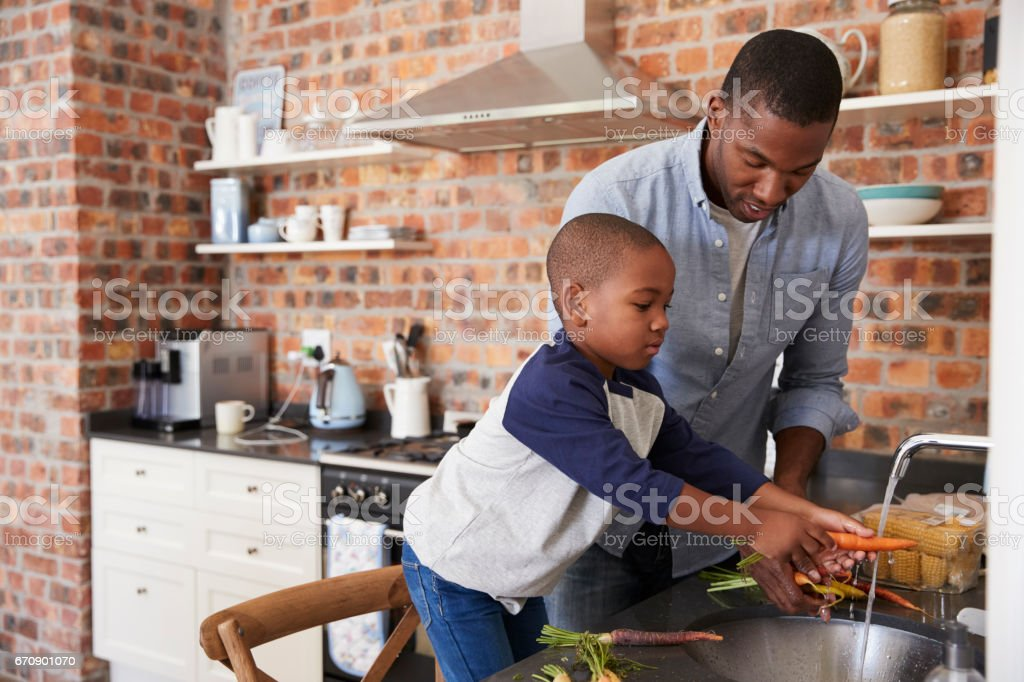 Son Helping Father To Prepare Vegetables For Meal In Kitchen stock photo