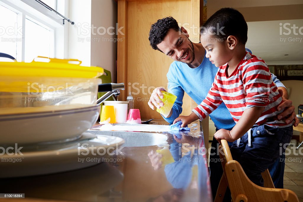 Son Helping Father To Wash Dishes In Kitchen Sink stock photo