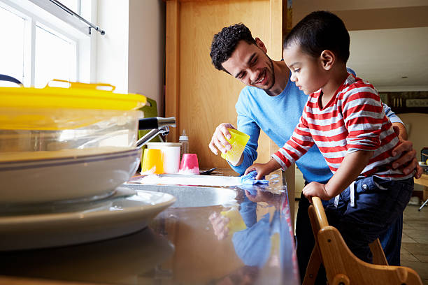 son helping father to wash dishes in kitchen sink - household chores stock photos and pictures