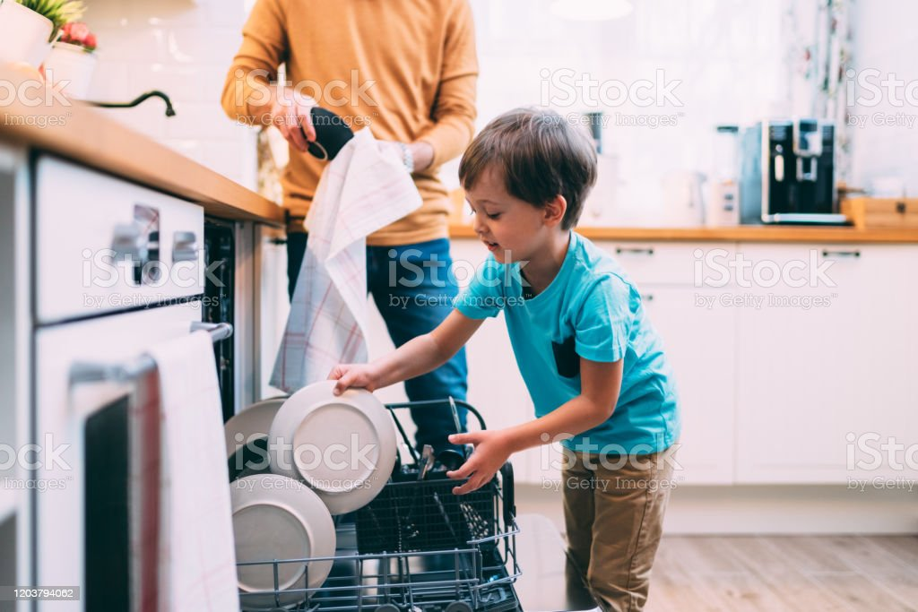 Son helping father with the dishwasher. Chores concept - Foto stock royalty-free di 4-5 anni