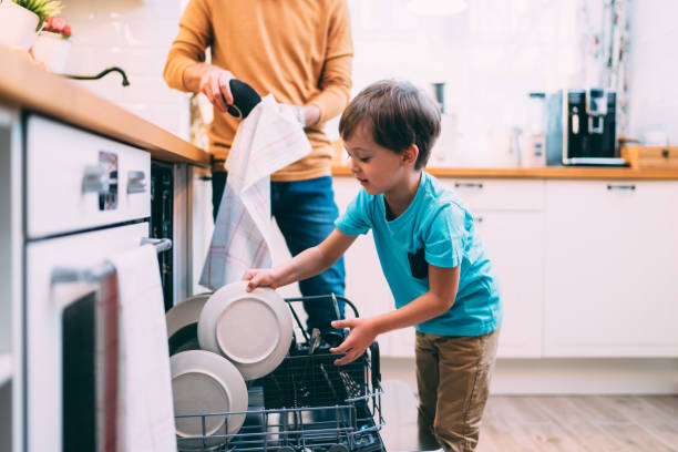 Son helping father with the dishwasher. Chores concept stock photo