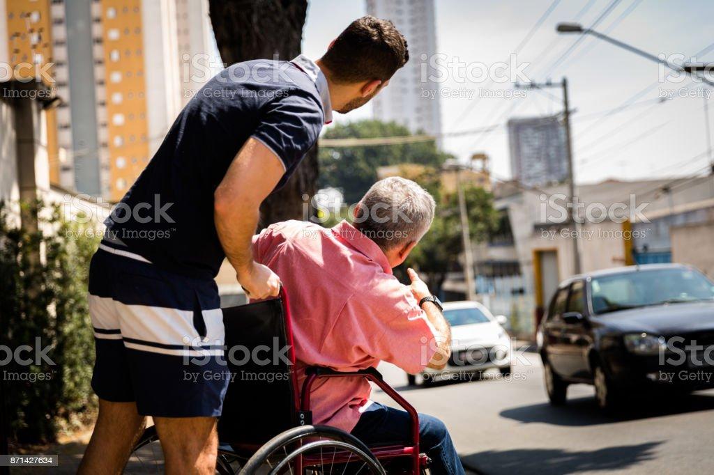 Hijo ayudando a su padre sentado en su silla de ruedas foto de stock libre de derechos
