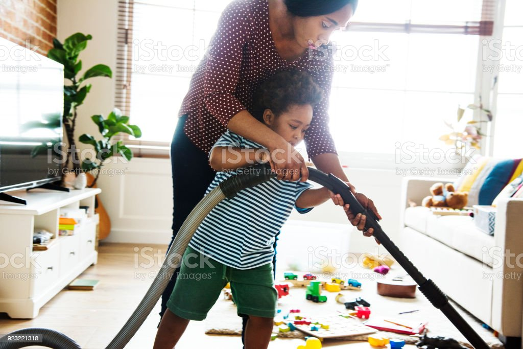 Son helping his mother clean the room stock photo