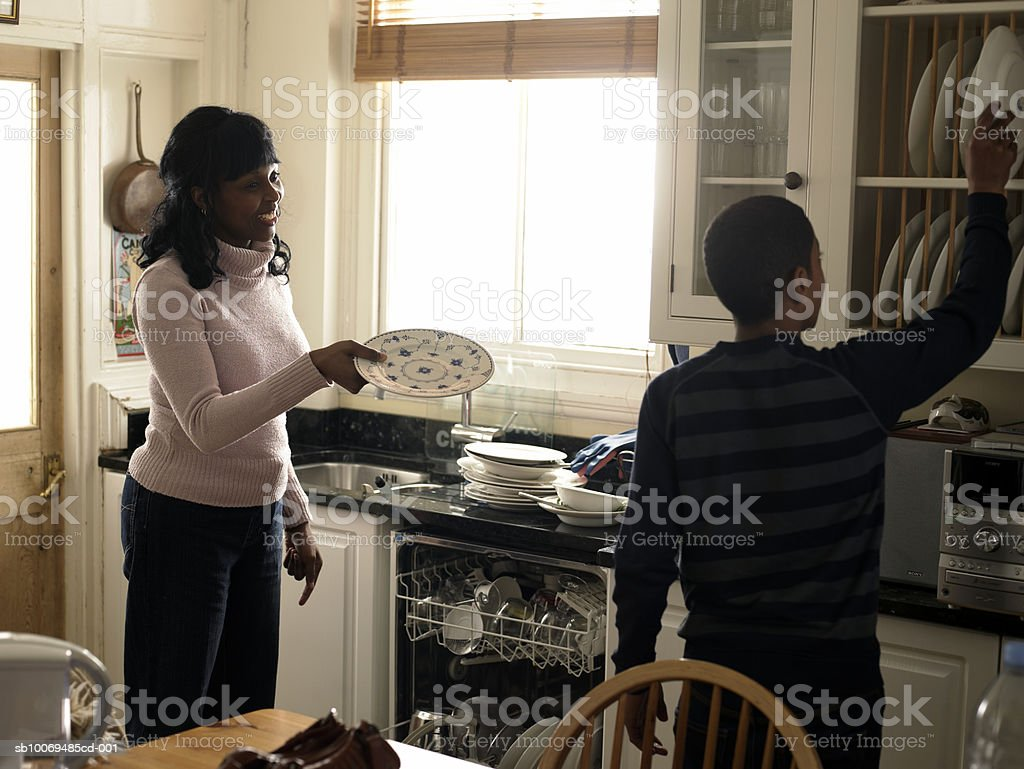 Son (12-13) helping mother unload dishwasher royalty-free stock photo