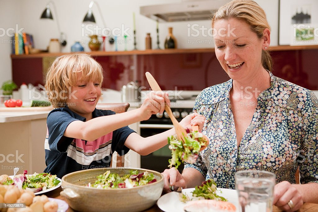 Son helping to serve salad for mother at the family dinner table stock photo