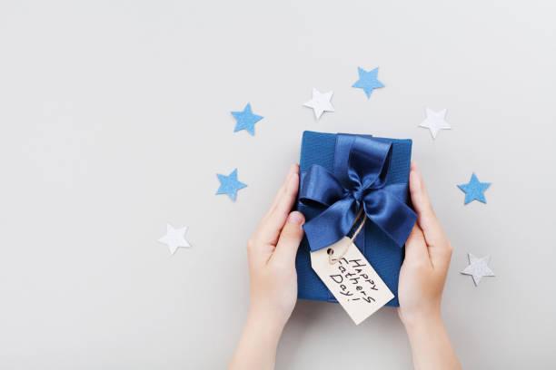 sohn hält ein geschenk oder eine geschenkbox mit happy väter tag tag. ferienkonzept. - vatertagsgrüße stock-fotos und bilder