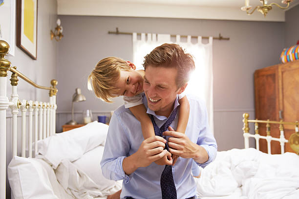 son hugging father as he gets dressed for work - day in the life series stock pictures, royalty-free photos & images