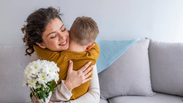 son hugging happy mother with flowers. - mothers day stock pictures, royalty-free photos & images