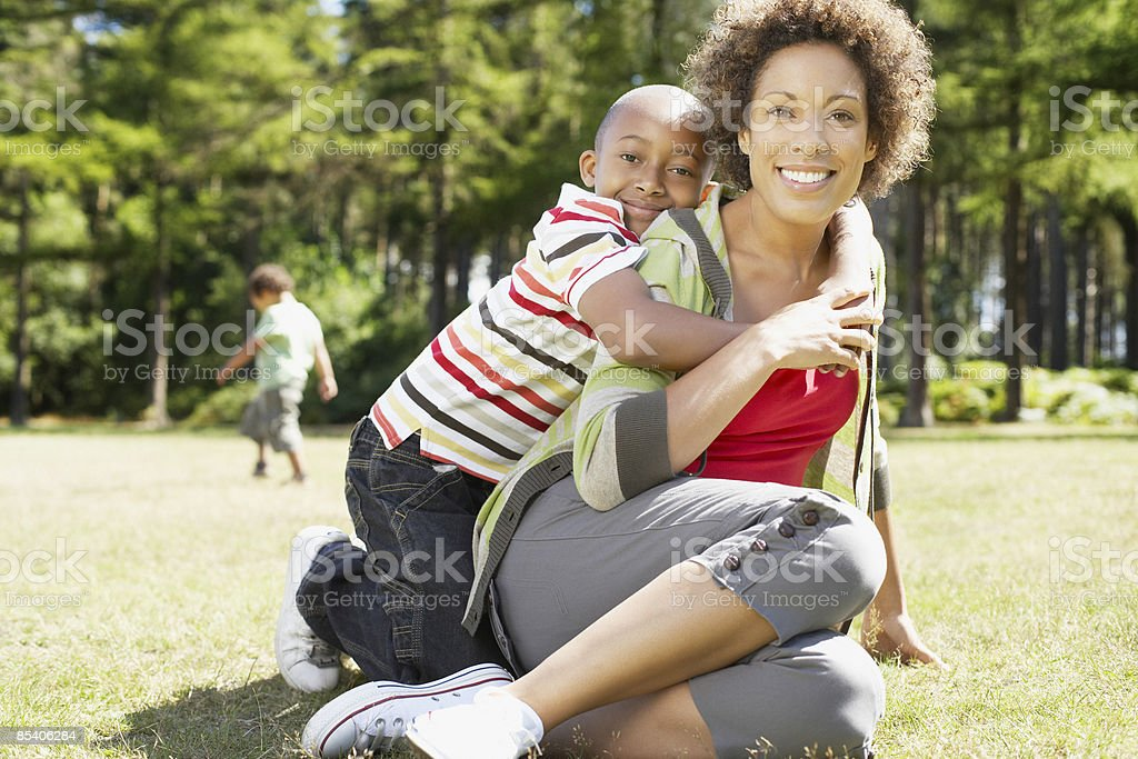 Son hugging mother in park royalty-free stock photo