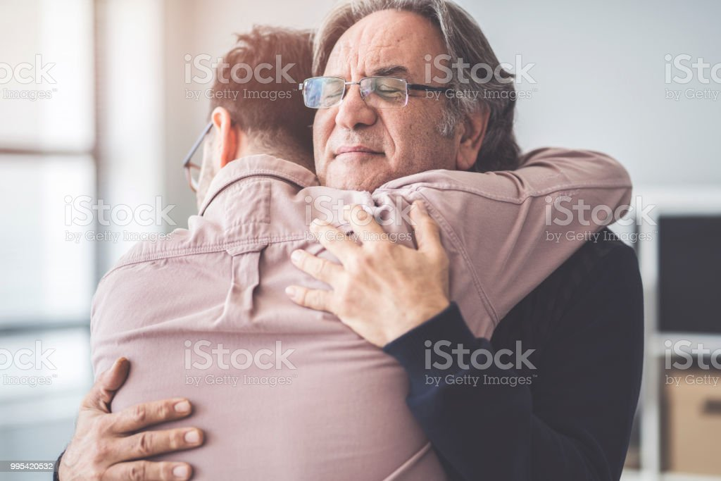 Son hugs his own father stock photo