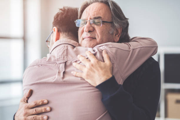 son hugs his own father - embracing stock pictures, royalty-free photos & images