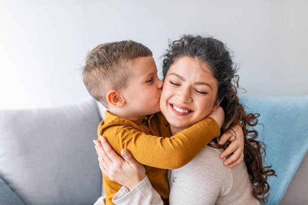 il figlio sta baciando sua madre. - bambino foto e immagini stock