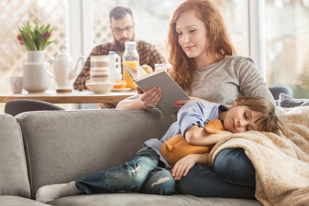 Son lying on mother's laps stock photo