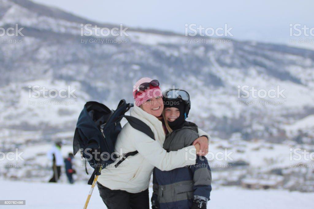 Son mother hug ski snow boarding stock photo