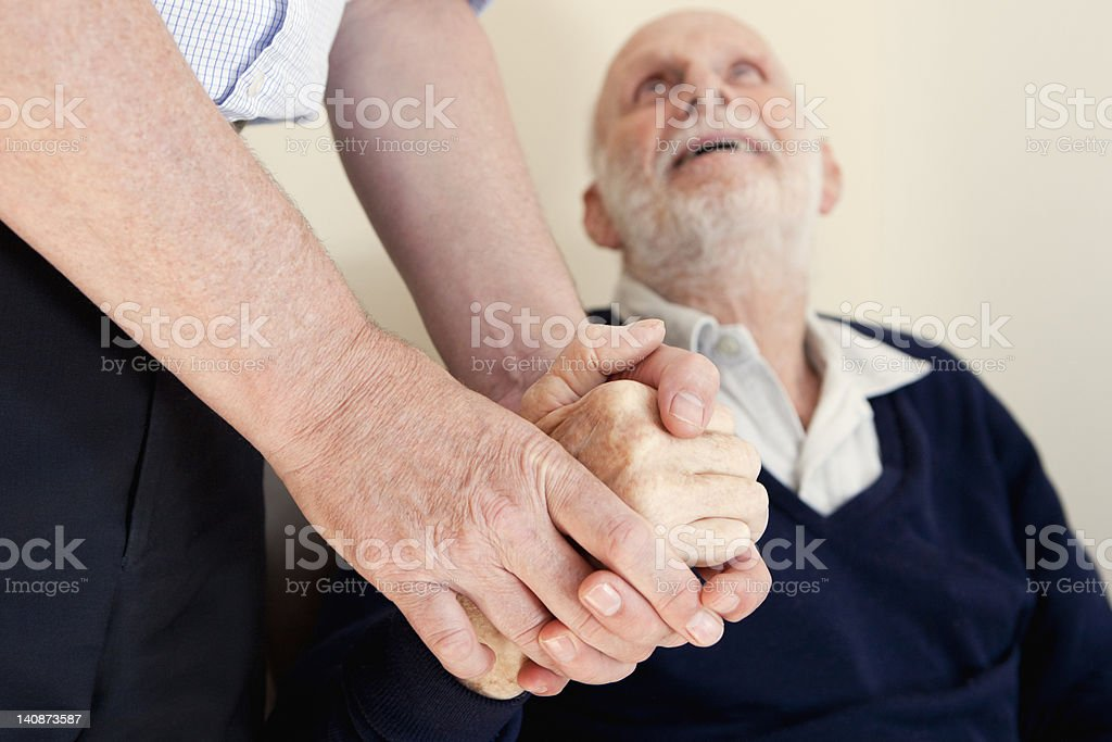 Son patting fathers hand stock photo