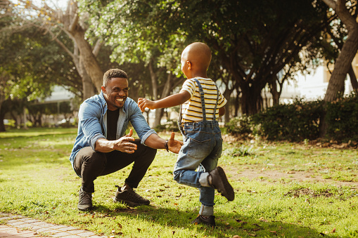 istock Son running into father's arms 1136387215