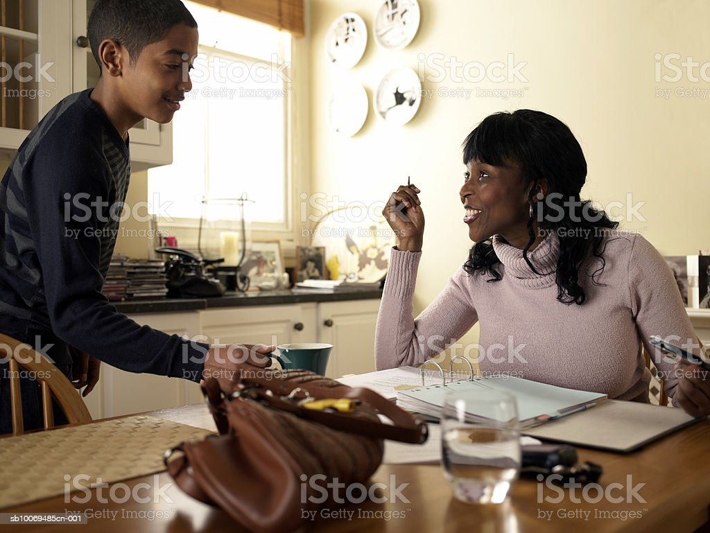 Son (12-13) serving tea to his mother sitting by paperwork at kitchen table royalty-free stock photo