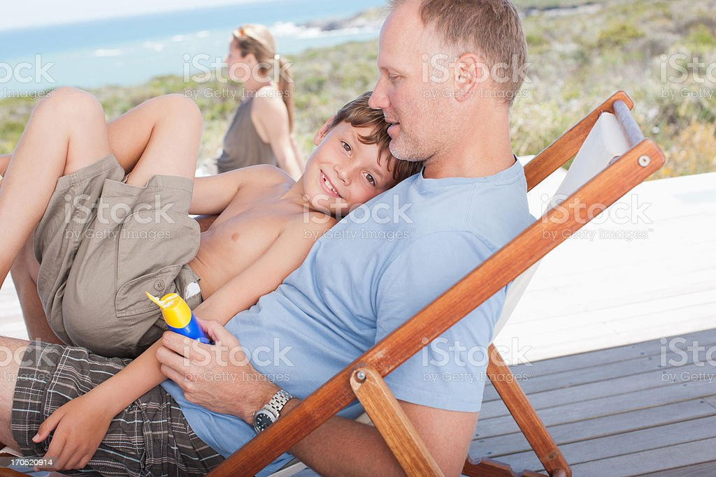 Son sitting in father's lap on deck royalty-free stock photo