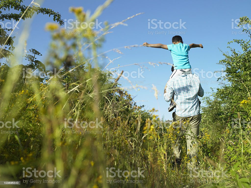 Son sitting on fathers shoulders royalty-free stock photo