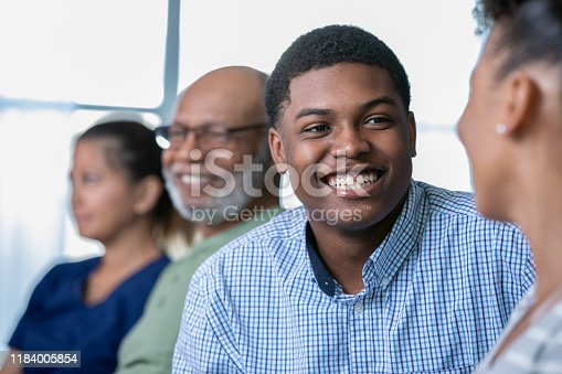 640177838 istock photo Son smiling at mother during family seminar or workshop 1184005854