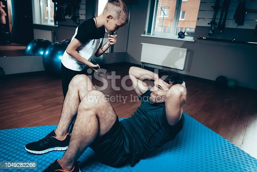 997711042istockphoto Son Support To Father While Doing Press Exersices. 1049282266