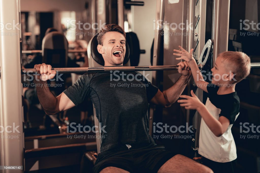Son Support To Father While Lifting The Barbell. stock photo