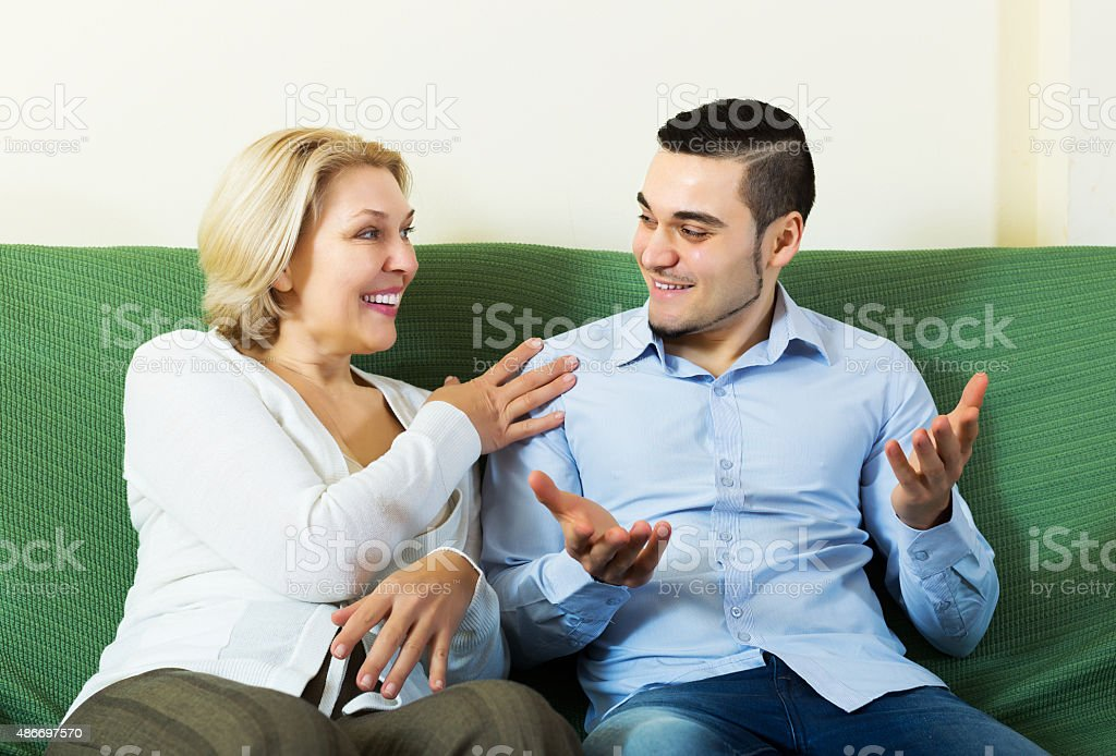 Son talking with senior mother stock photo