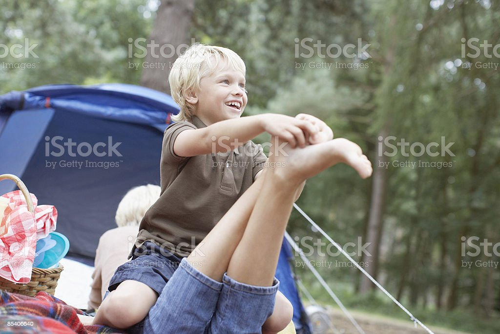Son tickling mothers foot in campsite royalty-free stock photo