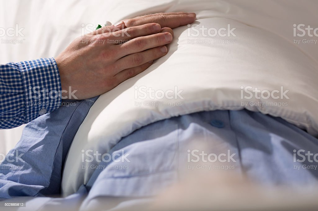 Son touching ill father's hand stock photo