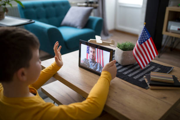 Son video chats with his father in military stock photo