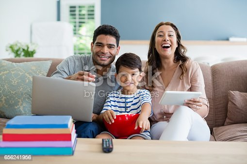 1134439364 istock photo Son watching television while father and mother using laptop and digital tablet at home 656241956