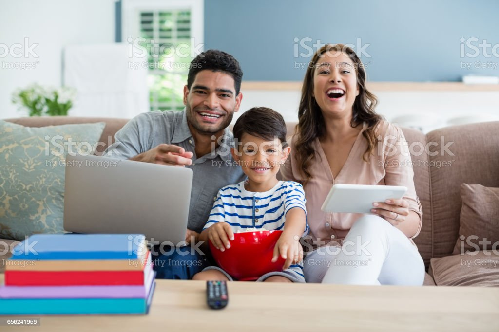 Son watching television while father and mother using laptop and digital tablet at home stock photo
