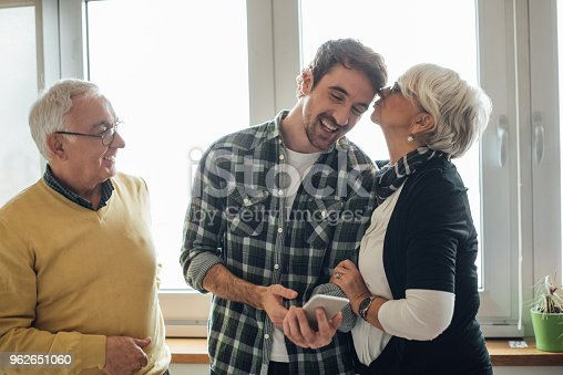 Young man looking at phone, his mother kissing him and father looking at them