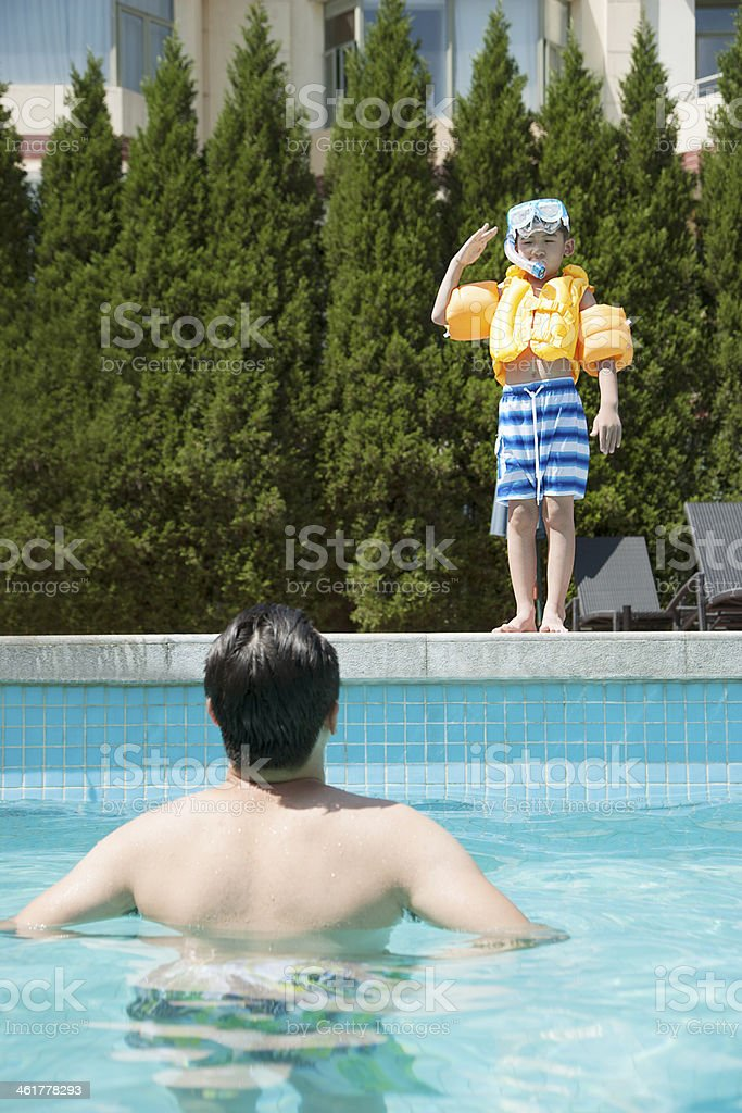 Son with snorkeling equipment standing by the pool stock photo