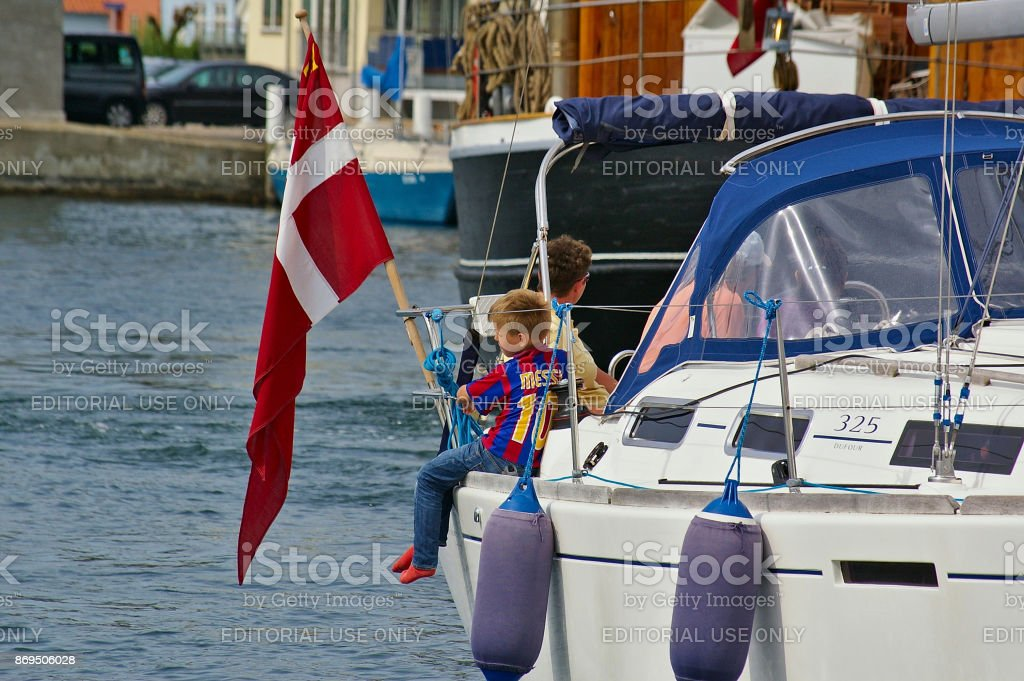 Sonderborg, Denmark - July 5th, 2012 - Young boy with soccer shirt sitting on the gunwhale of a white sailing yacht with the Danish flag next to him looking out over the water stock photo
