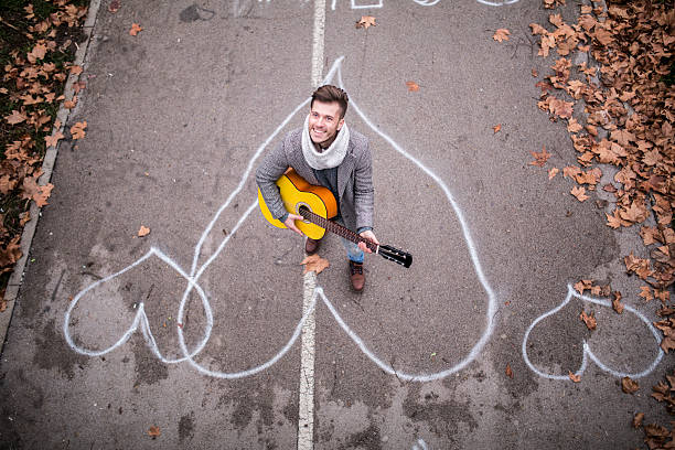 Song for her Guy playing a guitar from under the bridge serenading stock pictures, royalty-free photos & images