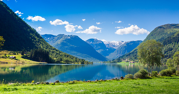 A Fjord of rich blue against a calm sky in a valley of Norway's Sogndal County.