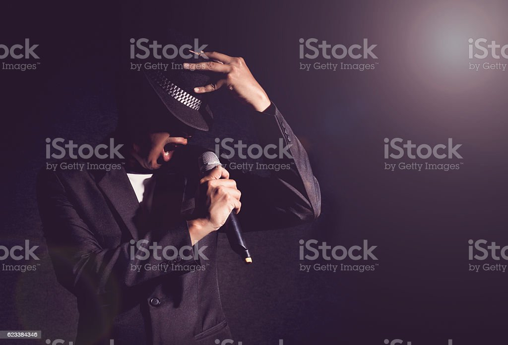 Songer hand holding the microphone and singing on black backgrou stock photo