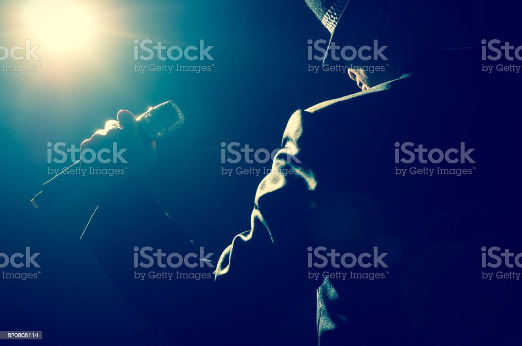 Songer hand holding the microphone with spot light and len flare, musical concept stock photo