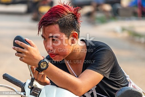 Vang Vieng, Laos - April 14, 2018: Local boy painting his lips on the street during the Lao New Year celebrations